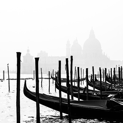 Romantic Italian city of Venice (Venezia), World Heritage Site: traditional Venetian wooden boats, gondolier and Roman Catholic church Basilica di Santa Maria della Salute in the misty background. B&W